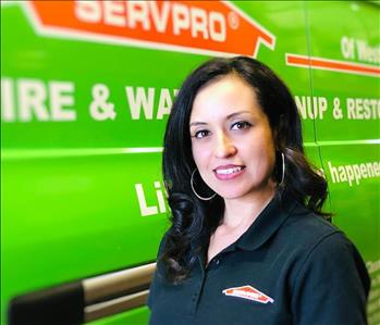 Adriana Castro standing in front of the green SERVPRO van