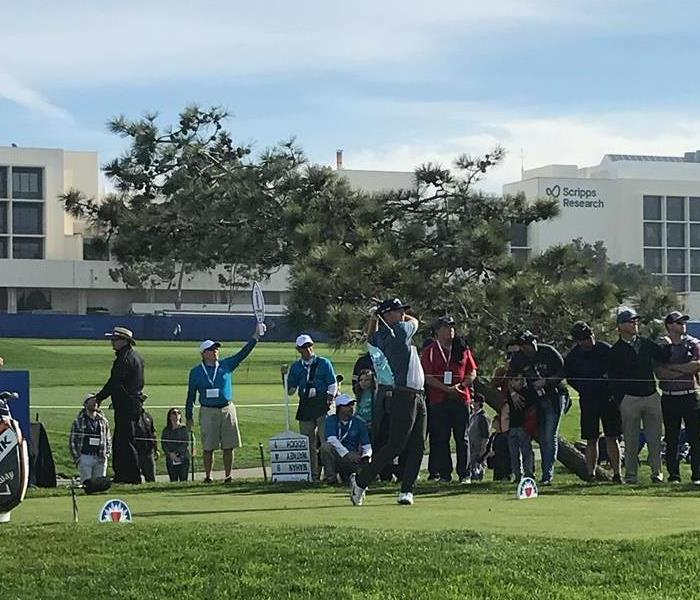 Crowd watching a man playing golf