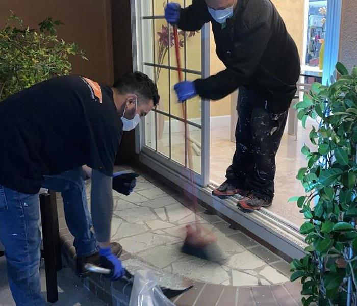 Two SERVPRO technicians cleaning up glass shards