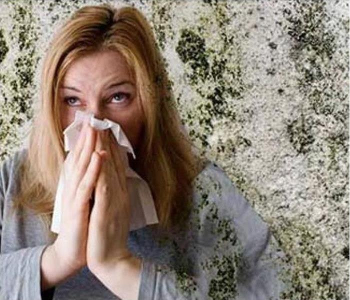 Woman blowing her nose into tissue, surrounded by mold