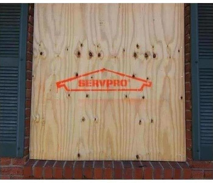 Wood used to board up window, SERVPRO logo spray painted