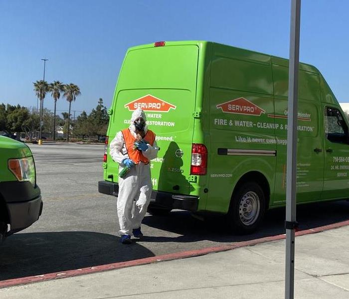 SERVPRO of Westminster worker in cleaning suit holding cleaning supplies