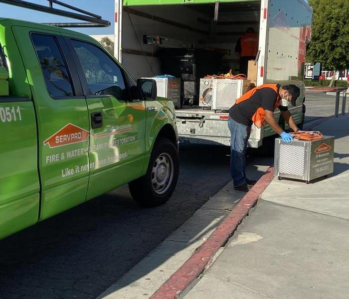 SERVPRO workers unloading supplies from green trucks