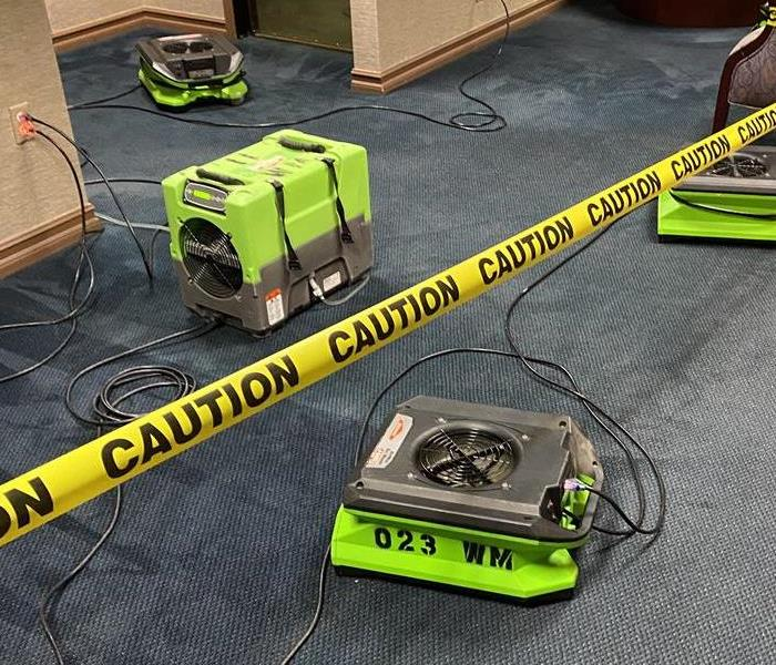 Green drying equipment placed on floor, caution tape present